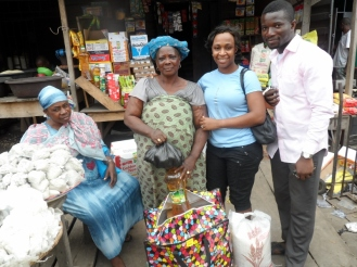 Ayo and Ifeoma encouraging a grandma with gifts